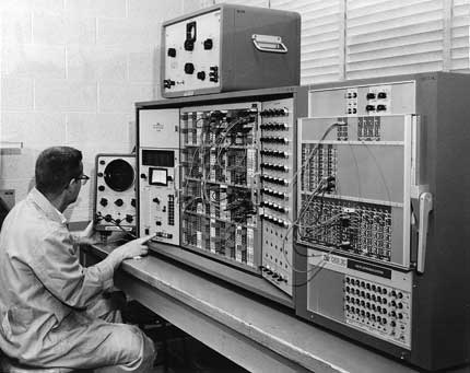 Photo of an electrical engineering professor in front of an old computer